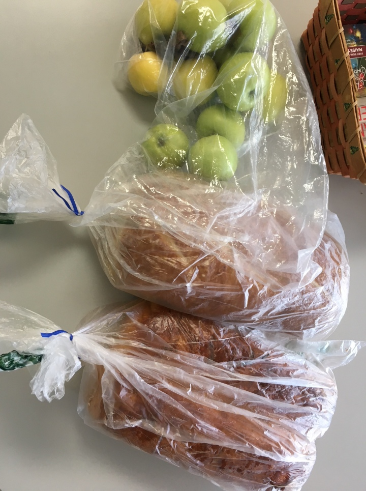 Two loaves of bread and a bag of apples.