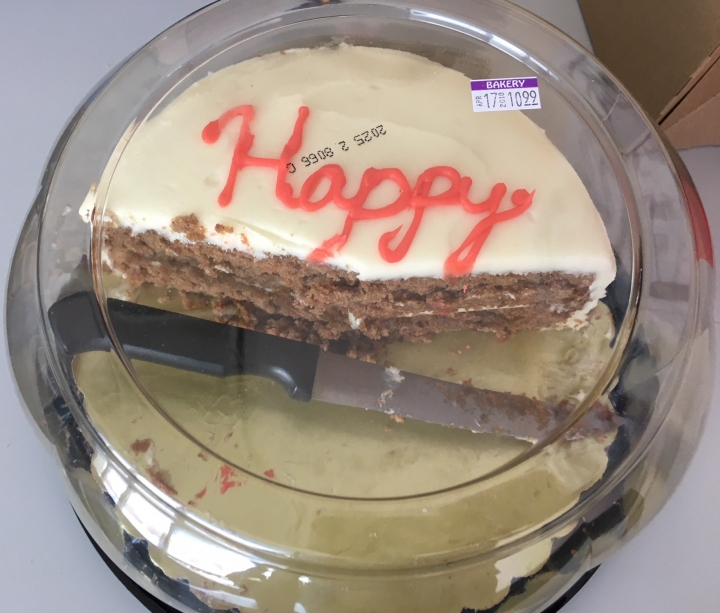 """Half a round cake with """"Happy"""" written on it."""