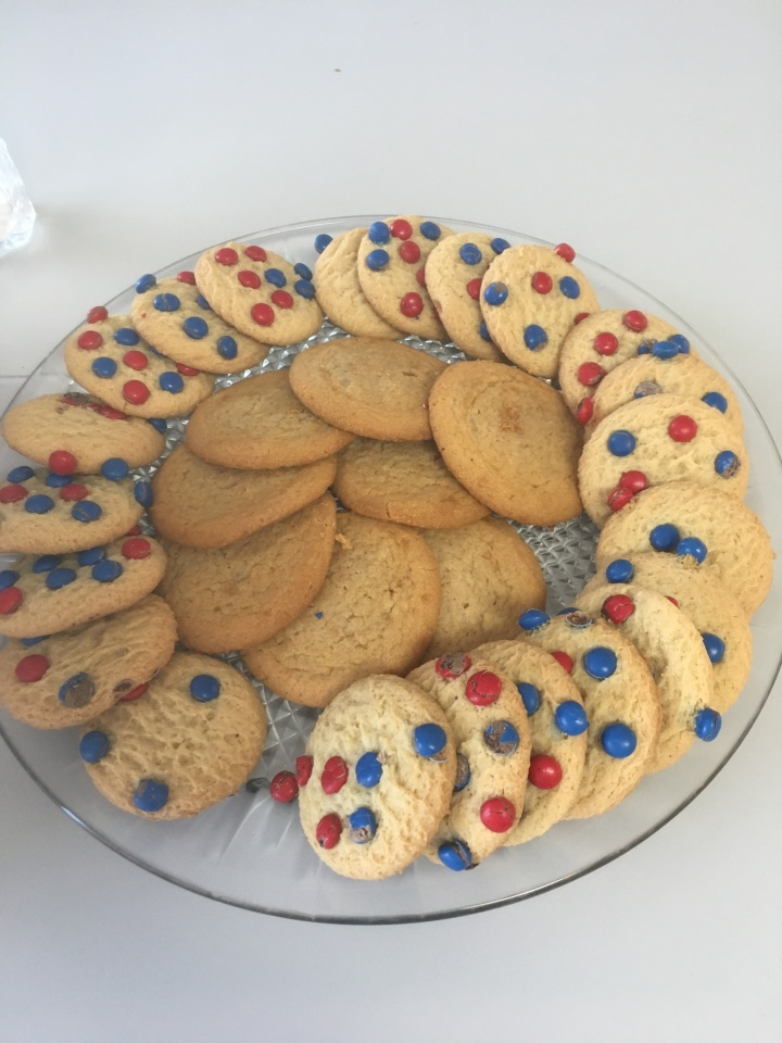 Plate of cookies, some with red and blue candies and others peanut butter.