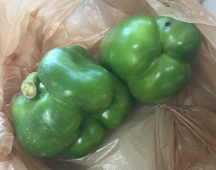 Two green peppers in a plastic bag