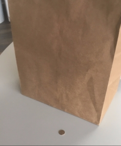 Paper bag of tomatoes with dime next to it